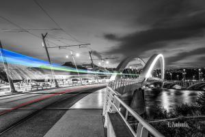 Schwarzweiss-Aufnahme an der Pont Raymond Barre Brücke in Lyon, Frankreich. Im Vordergrund zieht eine Bahn über die Brücke und hinterlässt einen farbigen Lichtschweif. Der Fluss Rotten ist rechts im Bild zu sehen und im Hintergrund befindet sich das Musée des Confluences.