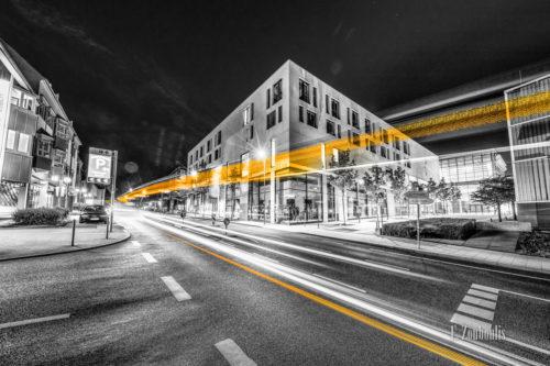 Schwarzweiss-Aufnahme an der Schwabengalerie in Vaihingen, Stuttgart. Im Vordergrund ist ein gelber Lichschweif zu sehen - ein Bus der über die Robert-Leicht-Straße fährt