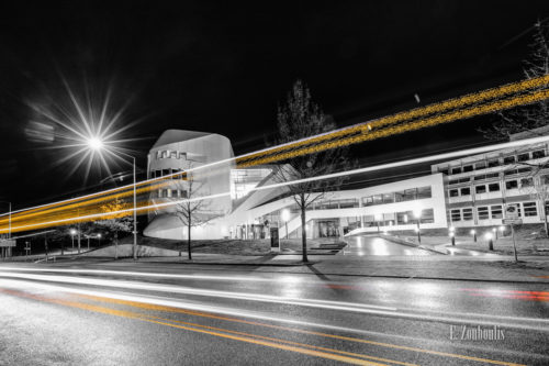 Nachtaufnahme in Schwarzweiß am Fraunhofer IAO Gebäude in Stuttgart Vaihingen. Rote und Gelbe Lichtschweife kennzeichnen den Verkehr auf der Nobelstraße
