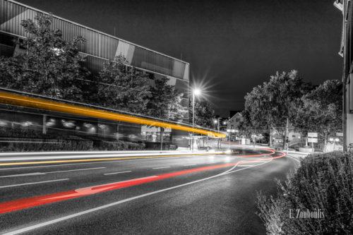 Schwarzweiss-Aufnahme an der Schwabengalerie in Vaihingen, Stuttgart mit Blick auf das Bürgerbüro. Im Vordergrund hinterlässt der Verkehr gelbe und rote Lichtschweife