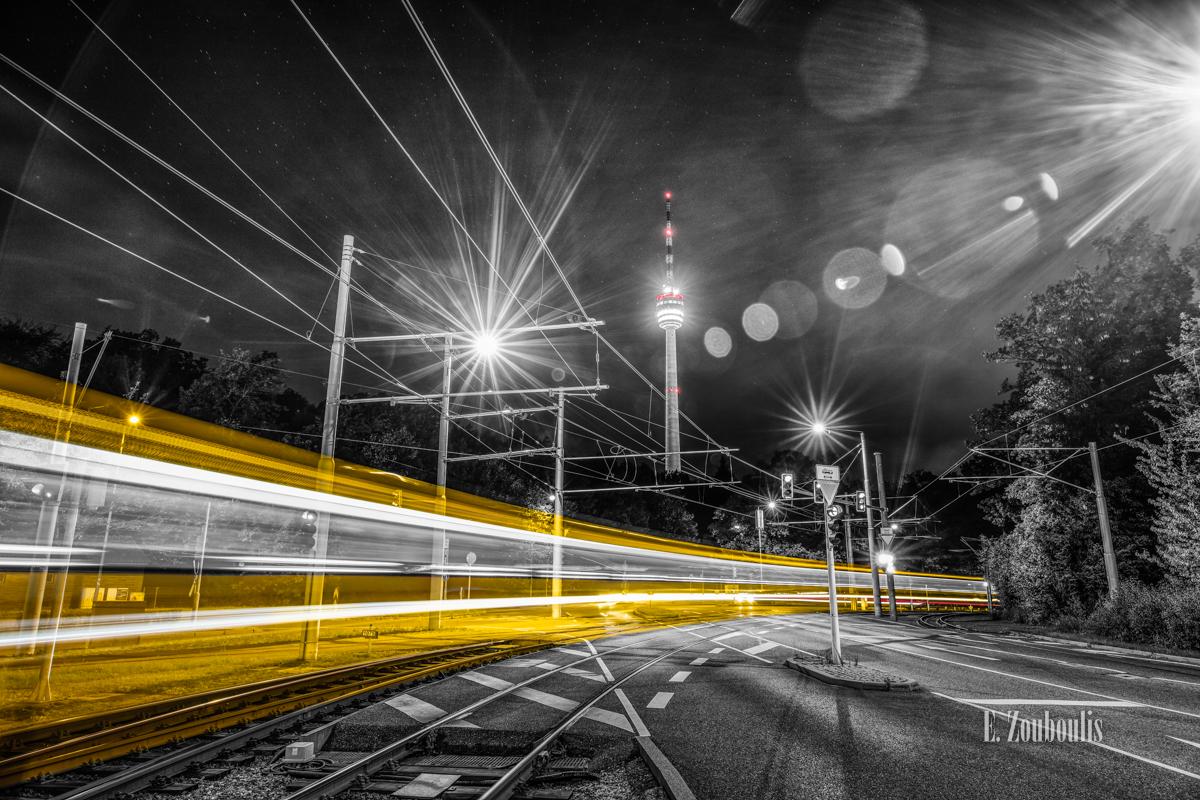 Schwarzweiß-Aufnahme mit roten und gelben Elementen mit Blick auf den Fernsehturm in Stuttgart Degerloch. Eine Bahn fährt am Betrachter vorbei und hinterlässt einen gelben Lichtschweif
