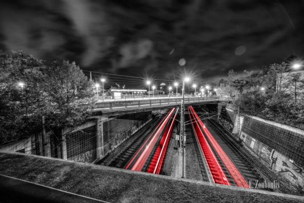 Schwarzweiss-Aufnahme an der Jurastraße in Stuttgart Vaihingen. Im Vordergrund sind vorbeifahrende Bahnen zu sehen, die einen roten Lichtschweif hinterlassen. In der Mitte des Bildes sieht man die Haltestelle Jurastraße und im Hintergrund ist der Vaihinger Colorado Turm zu sehen