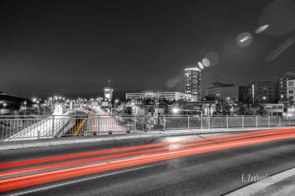 Schwarzweiss-Aufnahme am Pragsattel in Stuttgart. Der vorbeiziehende Verkehr hinterlässt farbige Lichtschweife. Im Hintergrund ist der Hochbunker und das Gebäude der Mercedes Benz Bank vor dem Skyline-Hochhaus zu sehen