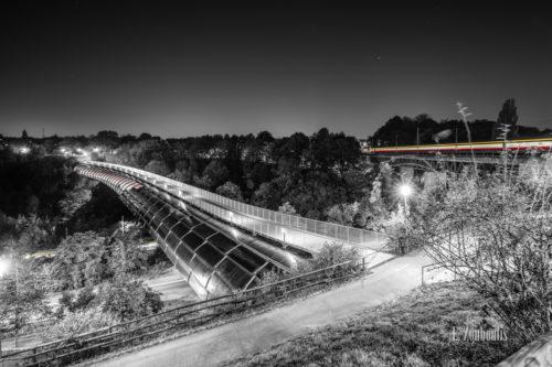 Schwarzweiss-Aufnahme am Österfeld / in Stuttgart Vaihingen. Im Vordergrund ist der Österfeldtunnel mit seiner einzigartigen Architektur zu sehen. Der Verkehr im Tunnel, an der Kaltentaler Abfahrt und rechts im Bild, hinterlässt rote und gelbe Lichtschweife