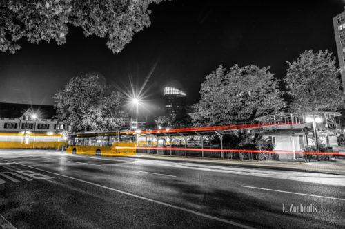 Schwarzweiss-Aufnahme am Bahnhof in Stuttgart Vaihingen. Im Vordergrund fährt ein Bus ein und zieht einen roten und gelben Lichtschweif hinter sich. Die Straßenbahn verlässt den Bahnhof in Lichtgeschwindigkeit. Im Hintergrund sieht man den Colorado Turm