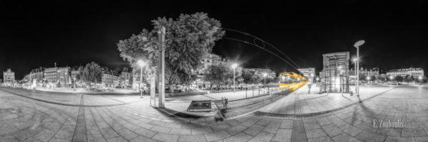 360 Grad Schwarzweiß Panorama am Marienplatz in Stuttgart Süd. Im Vordergrund ist eine einfahrende Zahnradbahn zu sehen, die einen gelben Lichtschweif hinter sich zieht.