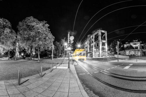 360 Grad Schwarzweiß Panorama am Eugensplatz in Stuttgart. In der Mitte des Bildes ist eine einfahrende Straßenbahn zu sehen, die einen gelben Lichtschweif hinter sich zieht. Rechts im Bild ist das Eiscafé Pinguin