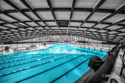 Schwarzweiß Aufnahme im Inneren des Badezentrum Sindelfingen. Das Wasser in den Becken ist in blau zu sehen. Seitliche Ansicht von oben auf das 50m Becken. Im Hintergrund ist der Sprungturm zu sehen
