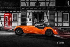 Schwarzweißaufnahme eines Orangenen Morgan 4/4. Fahrzeug in Orange in der Mitte des Bildes. Auf der linken Seite sieht man eine rote britische Telefonzelle vor dem Fachwerkhaus (Rathaus Gärtringen)