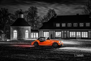 Schwarzweißaufnahme eines Orangenen Morgan 4/4. Fahrzeug in Orange in der Mitte des Bildes. Im Hintergrund ist die Villa Schwalbenhof in Gärtringen zu sehen