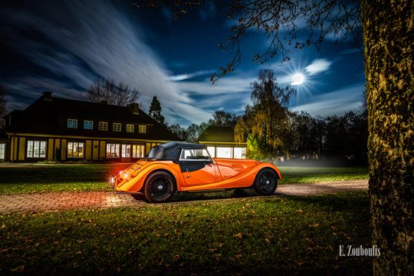 Aufnahme eines orangenen Morgan 4/4 vor der Villa Schwalbenhof in Gärtringen bei Vollmond