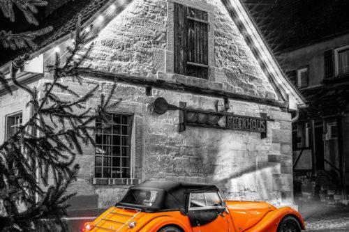 Schwarzweißaufnahme eines Orangenen Morgan 4/4. Fahrzeug in Orange in der Mitte des Bildes. Im Hintergrund ist das Backhaus am Marktplatz in Gärtringen zu sehen