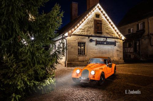 """Ein Morgan 4/4 mit seiner einzigartigen """"Morgan Orange"""" – Farbe vor dem Backhaus am Marktplatz in Gärtringen."""