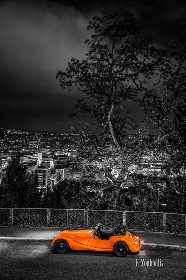 Schwarzweißaufnahme eines orangenen Morgan 4/4 Cabrio mit offenem Verdeck. Fahrzeug in Orange unten im Bilde. Im Hintergrund ist die Stuttgarter Sykline von Dobel aus zu sehen
