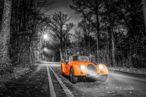 Schwarzweißaufnahme eines orangenen Morgan 4/4 Cabrio mit offenem Verdeck. Fahrzeug in Orange in der Mitte des Bildes. Im Hintergrund ist der Fernsehturm in Stuttgart Degerloch zu sehen