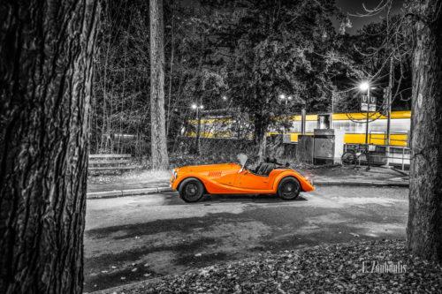 Schwarzweißaufnahme eines orangenen Morgan 4/4 Cabrio mit offenem Verdeck. Fahrzeug in Orange in der Mitte des Bildes zwischen zwei Bäumen. Im Hintergrund ist eine vorbeifahrende Straßenbahn zu sehen. Aufnahme in Stuttgart.