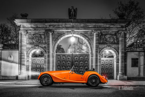 Schwarzweißaufnahme eines orangenen Morgan 4/4 Cabrio mit offenem Verdeck. Fahrzeug in Orange in der Mitte des Bildes. Im Hintergrund sieht man die Tore der Robert Bosch Stiftung in Stuttgart