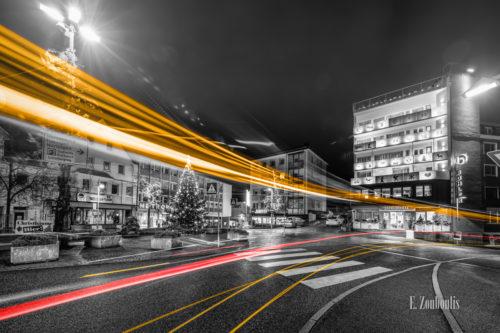 Schwarzweiß-Aufnahme am Postplatz in Böblingen mit gelben und roten Lichtschweifen, die den vorbeiziehenden Verkehr kennzeichnen