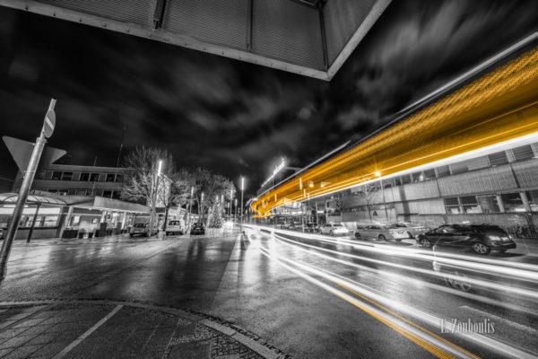 Schwarzweiß-Aufnahme von einem vorbeifahrenden Bus am Bahnhof in Böblingen. Gelbe und rote Lichtschweife kennzeichnen den Verkehr vor dem Mercaden-Einkaufszentrum