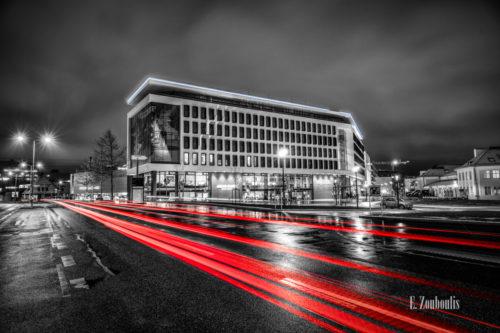 Schwarzweiss-Aufnahme an der Motorworld in Böblingen bei Stuttgart. Im Vordergrund sind rote Lichtschweife vom vorbeifahrenden Verkehr zu sehen. Im Hintergrund befindet sich das V8 Hotel