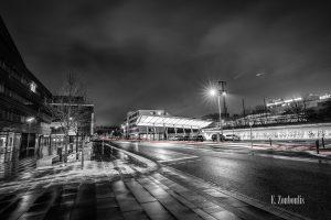 Schwarzweiß-Aufnahme am Bahnhof in Böblingen. Im Vordergrund liegt ein wenig Schnee, die Straße und der Gehweg sind nass. Auf der Straße Fähr ein Auto vorbei und hinterlässt einen roten Lichtschweif. In der Mitte des Bildes sieht man die Dachkonstruktion, die zu den Gleisen führt