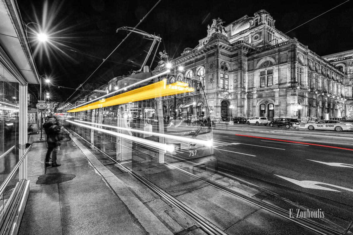 Schwarzweiß-Fotografie am Burgring in Wien mit einfahrender Straßenbahn in gelber Aufschrift vor der Wiener Staatsoper