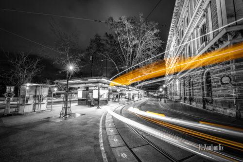 Schwarzweiß-Aufnahme einer Straßenbahn mit gelbem Lichtschweif vor einem Würstelstand am Burgring in Wien