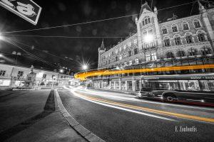 Schwarzweiß-Fotografie am Margaretenplatz in Wien mit gelbem Lichtschweif, der den Verkehr kennzeichnet.