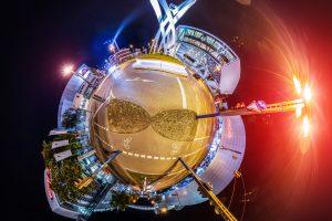 360 Grad Foto am Porscheplatz Stuttgart bei Nacht. Zu sehen ist ein kleiner Planet der den Kreisverkehr um die Porsche-Zentrale, das Porsche Museum und die Beleuchtung der Stadt zeigt.