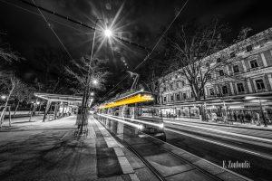 """Schwarzweiß-Fotografie am Burgring in Wien mit einfahrender Straßenbahn in gelber Aufschrift """"1 Prater Hauptallee"""""""