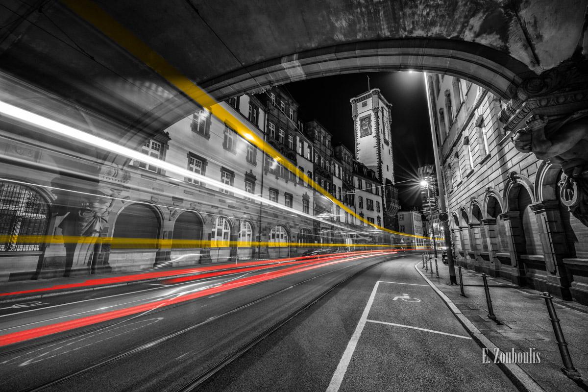 Fotografie an der Bethmannstraße am Römer Frankfurt bei Nacht mit Blick auf den Turm vom Standesamt. Schwarz Weiß Bild mit gelben und roten Light Trails einer vorbeiziehenden Straßenbahn