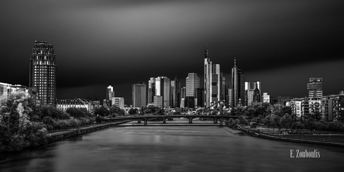 Die Skyline Frankfurt als Schwarz Weiß Fotografie mit Blick auf die Wolkenkratzer und den Main. Bild aus einer aufwendigen Langzeitbelichtung entstanden.