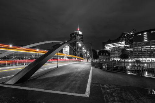 Fotografie am Sandtorkai in Hamburg am Hafen bei Nacht mit Blick auf die Elbphilharmonie. Schwarz Weiß Bild mit gelben und roten Light Trails des vorbeiziehenden Verkehrs