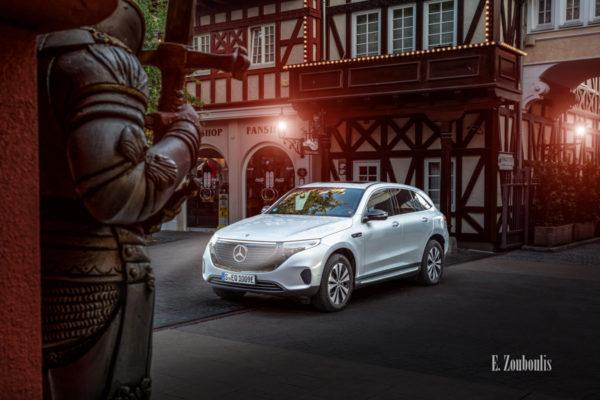 Bild eines Mercedes Benz EQC aufgenommen im Europa Park. Seitliche Ansicht von vorn. Im Vordergrund ist ein Ritter zu sehen