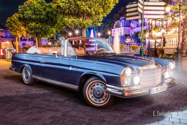 Ein 1971 Mercedes-Benz 280 SE nachts im Europa-Park seitlich von vorne mit den Lichtern des Europapark im Hintergrund