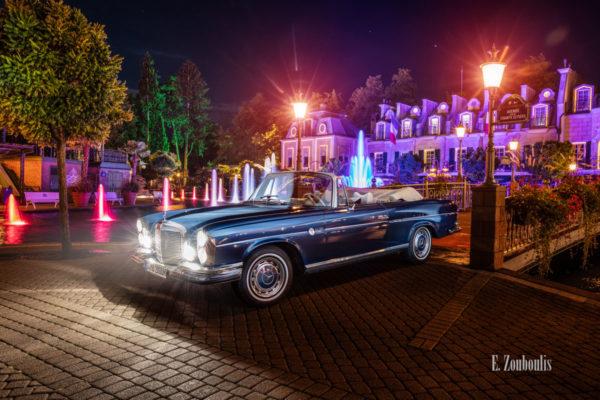 Ein 1971 Mercedes-Benz 280 SE nachts im Europa-Park seitlich von vorne
