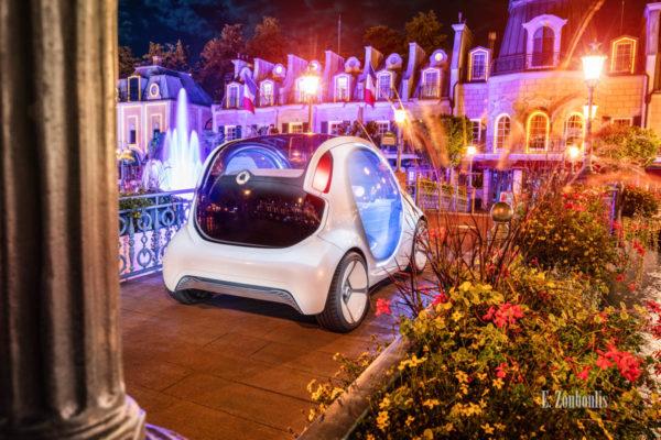 Wandbild eines Smart Vision EQ. Aufgenommen nachts im Europa Park seitlich von hinten. Im Vordergrund sind eine Säule und Pflanzen zu sehen