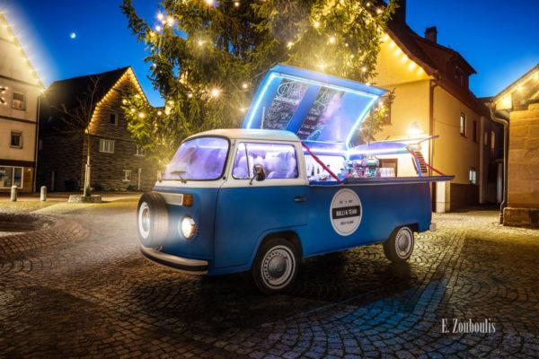 Wandbild eines Volkswagen Bulli T2 aus dem Jahr 1970. Der Oldtimer ist als Bar umgebaut worden und leuchtet vor einem Weihnachtsbaum